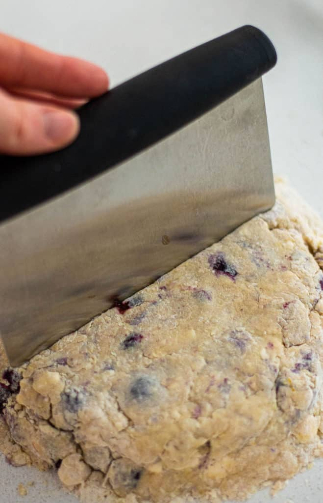 Cutting homemade scones with a bench scraper.