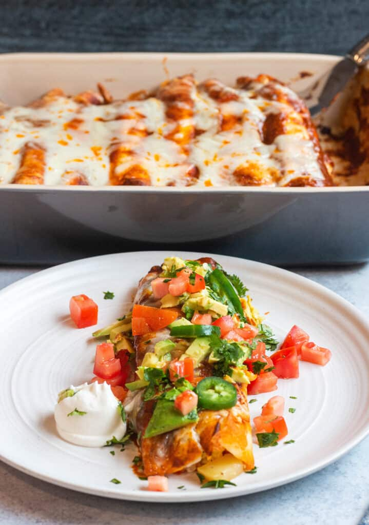 Homemade breakfast enchiladas topped with jalapeños, cilantro, tomatoes, avocado and sour cream.